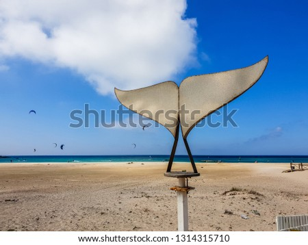 Picture of a Wind spinner in Tarifa, Andalusia, Spain. Beach with blue sky and clouds in the background.