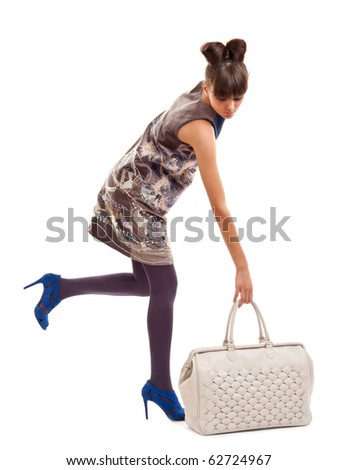 picture of a woman in a dress and high heels shoes picking up a big purse