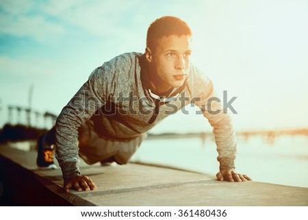 Picture of a young athletic man doing push ups outdoors.Fitness and exercising outdoors urban environment.Selective focus