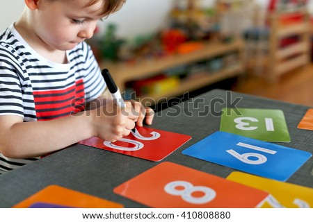 Picture of a young boy learning to write numbers on colorful cards with a focus on his hand and his pen