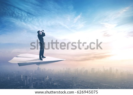 Photo of Picture of a young businessman standing on a paper plane while flying above a city and looking through a binoculars