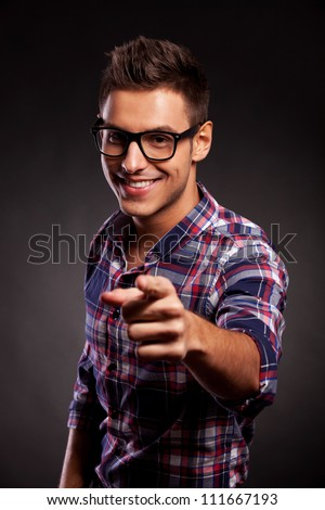 Picture of a young casual man with spectacles pointing at the camera, over black background