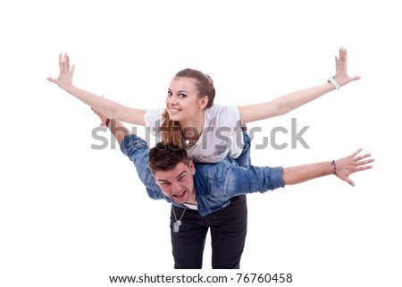 picture of a young couple having fun - woman on the back of her boyfriend, simulating flying - stock photo