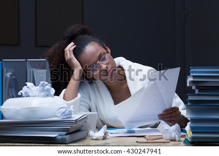 Picture of a young female student revising at night, sitting by a desk filled with books and papers