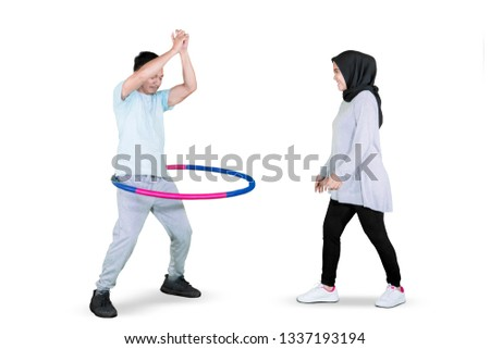 Picture of a young man and his wife exercising with a hula hoop in the studio, isolated on white background