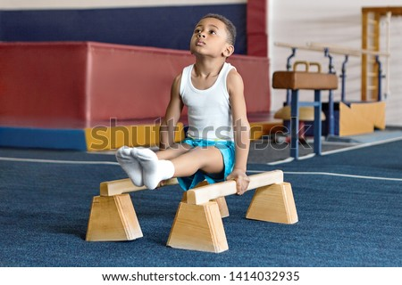Picture of adorable dark skinned little gymnast competing on parallel bars. Hardworking talented African child exercising at gym, doing acrobatic moves, demonstrating strength, agility and flexibility