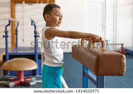 Picture of adorable happy dark skinned atheltic child in blue shorts and white t-shirt posing at gym with gymnastics equipment in background, holding hands on handles, going to perform routine