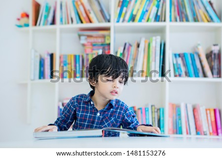 Picture of adorable little boy reading a book while studying in the library with bookcase background