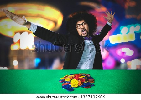 Picture of Afro man celebrating his winning with chips on table after gambling in the casino