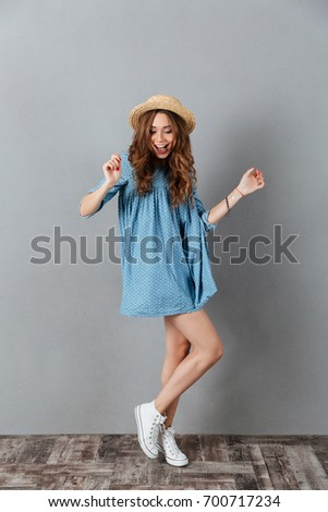 Picture of amazing young caucasian lady dancing over grey background. #700717234