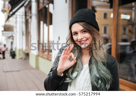 Picture of amazing young woman wearing hat walking on the street and looking at camera while make okay gesture.
