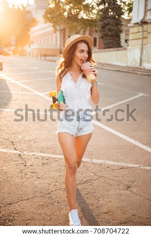 Picture of amazing young woman with skateboard outdoors drinking juice. Looking aside.