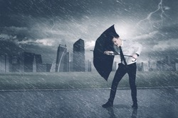 Picture of American businessman using an umbrella while protecting himself from storm