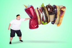 Picture of an Asian obese man wearing sportswear while punching unhealthy foods in green screen background