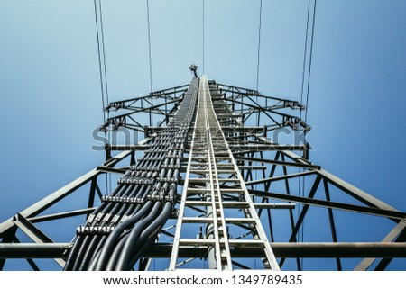 Picture of an electrical tower or pylon, blue sky in the background. Power grid or smart grid.  #1349789435