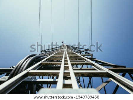 Picture of an electrical tower or pylon, blue sky in the background. Power grid or smart grid.  #1349789450