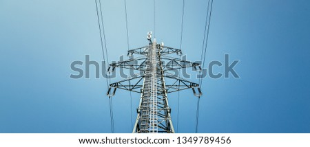Picture of an electrical tower or pylon, blue sky in the background. Power grid or smart grid.  #1349789456