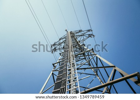Picture of an electrical tower or pylon, blue sky in the background. Power grid or smart grid.  #1349789459