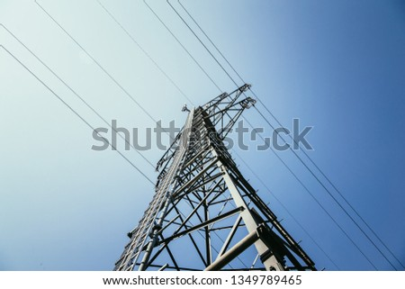 Picture of an electrical tower or pylon, blue sky in the background. Power grid or smart grid.  #1349789465