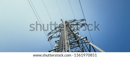 Picture of an electrical tower or pylon, blue sky in the background. Power grid or smart grid.  #1361970851
