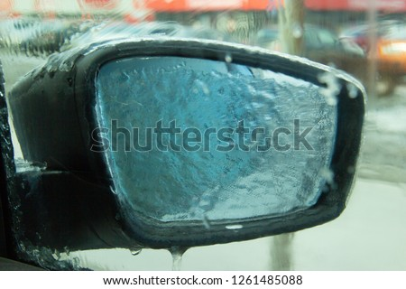 Picture of an iced car mirror and window. Photographed from inside the cabin through a frozen window. Blurred