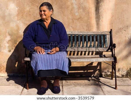 Picture of an old lady sitting on a bench in the village of Sotirianika, southern Greece