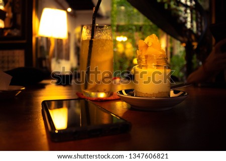 Picture of An Orange Cheesecake with A glass of Lime Juice as complement and A phone on a table