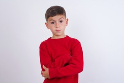 Picture of angry Cute Caucasian kid boy wearing knitted sweater against white wall looking camera.