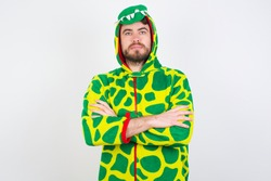 Picture of angry Young caucasian man wearing a pajama standing against white background looking camera.