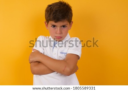 Picture of angry young handsome little boy crossing arms standing isolated over yellow background. Looking at camera with disappointed expression. Stock foto ©