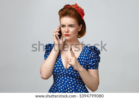 Picture of angry young mother in vintage outfit having strict look, raising index finger in front of her as warning sign, talking on smart phone with her naughty son who is still out with friends #1094799080