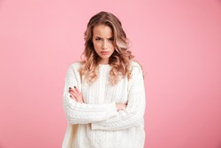 Picture of angry young woman standing isolated over pink background. Looking camera.