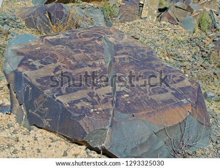 Picture of antelopes, dogs, wolves & people with bows on rocks at Tamgaly National Petroglyph Park (Kazakhstan). Bronze age.