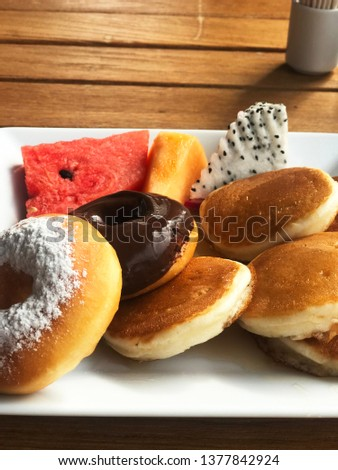 Picture of assorted pancakes, fruits (pitaya, watermelon, mango)  and donuts on a plate with chocolate frosted glazed. - Image