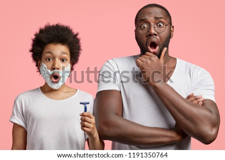 Picture of astonished dark skinned father keeps hand under chin, gives lessons how to shave to his small teenage son, notice something unbelievable. Shocked African American child with shaving gel