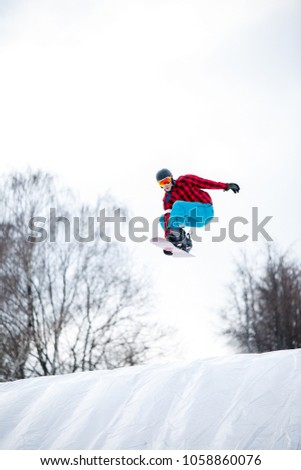 Picture of athlete in helmet riding snowboard from snow slope #1058860076