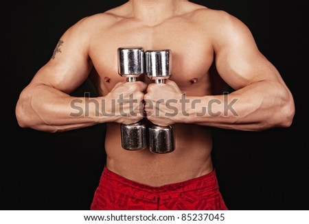 Picture of athlete male with two dumbbells isolated on black background