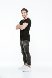 Picture of attractive cheerful young man dressed in black t-shirt standing with arms crossed over white background.