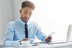 Picture of attractive young African American manager dressed in formal wear sitting at his workspace with cell phone, looking at information on his credit card while signing up for mobile banking app