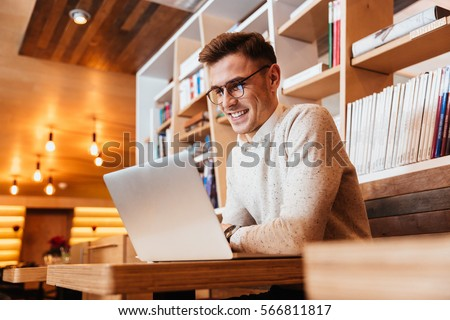 Picture of attractive young happy man wearing eyeglasses sitting in cafe while using laptop computer.