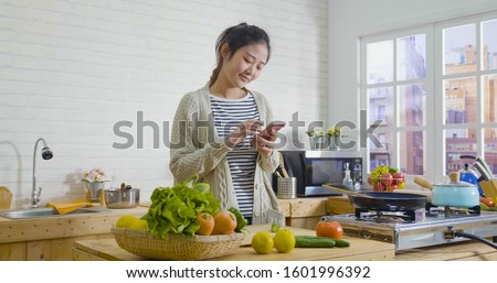Picture of beautiful asian chinese woman cooking vegetables in cozy wooden kitchen while looking recipe on smartphone. young girl browsing website on tutor cooking class and smiling checking fruits.