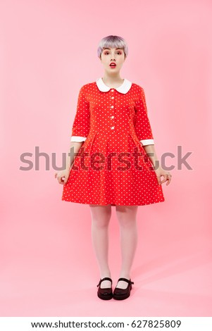 Picture of beautiful dollish girl with short light violet hair wearing red dress over pink background. Stock photo ©