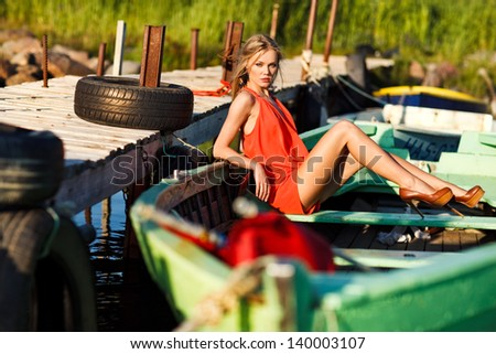 picture of beautiful girl in red dress sitting in a boat