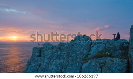Picture of beautiful sunset with the view of the high cliff, where a men making a photo. Bretagne. - stock photo