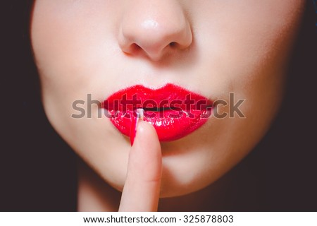 Picture of beautiful young lady with bright makeup shushing. Closeup of red lips and finger on dark blurred background.
