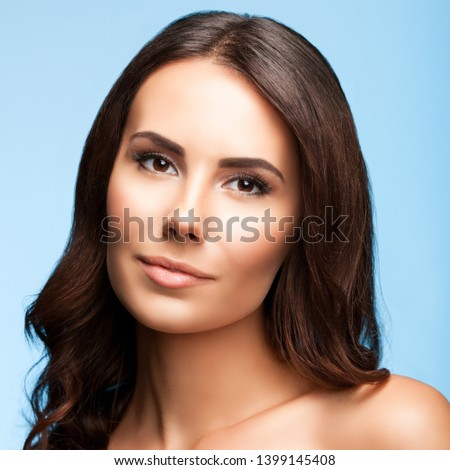Picture of beautiful young woman with naked shoulders, against blue color background