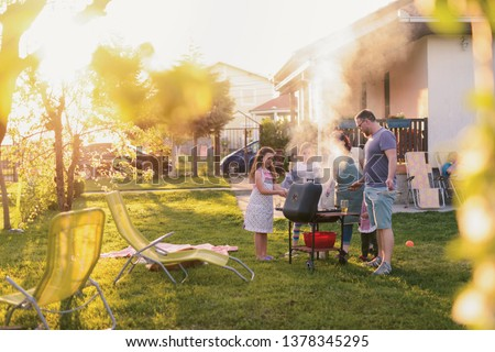Picture of big happy family making barbeque in their backyard. Family time on sunny summer day.