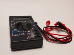 Picture of black digital multimeter or AVO meter for measuring electrical stuff such as voltage, resistance, and current. Shoot on a white isolated background