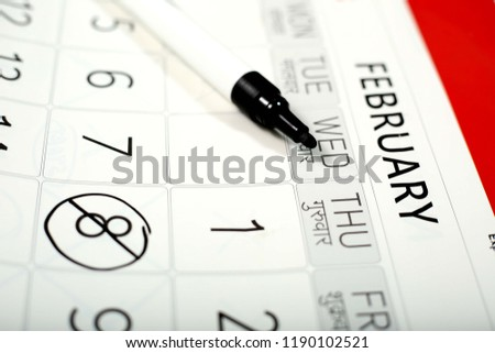 Picture of black marker on the white calendar.
