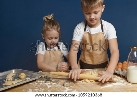 Picture of blonde 7 year old boy with hair knot helping his elderly brother to bake cookies at kitchen counter. Two preschoolers making dough for pasty, using rolling pin, milk and eggs on table stock photo